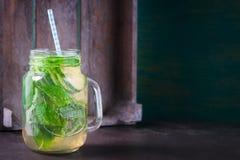 鲜美五颜六色的饮料用冷的绿茶、薄菏和黄瓜在一个玻璃瓶子在葡萄酒背景 免版税库存照片