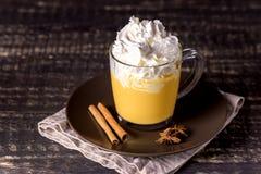 鲜美南瓜拿铁用香料鞭打了在上面的奶油在一个黑暗的木背景秋天热的饮料 免版税库存照片