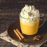 鲜美南瓜拿铁用香料鞭打了在上面的奶油在一个黑暗的木背景秋天热的饮料 免版税库存图片