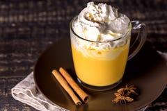鲜美南瓜拿铁用香料鞭打了在上面的奶油在一个黑暗的木背景秋天热的饮料 库存照片