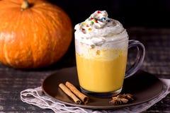 鲜美南瓜拿铁用香料鞭打了在上面的奶油在一个黑暗的木背景秋天热的饮料 图库摄影