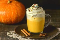 鲜美南瓜拿铁用香料鞭打了在上面的奶油在被定调子的一个黑暗的木背景秋天热的饮料 免版税库存图片