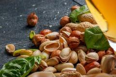 鲜美咸破裂的开心果、新鲜的蓬蒿叶子和嘎吱咬嚼的坚果特写镜头在灰色背景 可口快餐 库存图片