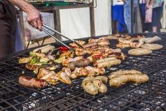 鲜美夏天烤肉烤在热的火焰状煤炭的用香肠,牛排,鸡翼卤汁,大蒜,葱,蕃茄和 免版税库存图片
