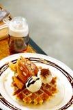 鲜美奶蛋烘饼和香草冰淇淋集合服务与香蕉糖涂层冠上用在白色板材的巧克力汁在绿色庭院里 免版税库存图片