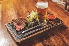鲜美嫩肉和冷的贮藏啤酒在客栈 免版税库存照片