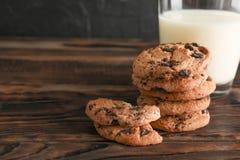鲜美巧克力曲奇饼和杯在木桌上的牛奶 免版税库存图片
