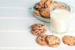 鲜美巧克力曲奇饼和杯在木桌上的牛奶 免版税库存照片