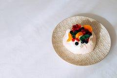 鲜美帕夫洛娃点心用白色蛋白甜饼、奶油和果子 免版税库存照片