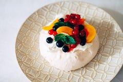 鲜美帕夫洛娃点心用白色蛋白甜饼、奶油和果子 库存照片