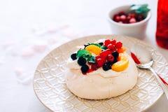 鲜美帕夫洛娃点心用白色蛋白甜饼、奶油和果子 免版税图库摄影