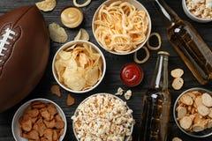 鲜美快餐和啤酒为观看在桌上的橄榄球做准备 免版税库存照片