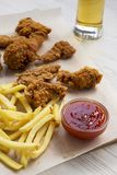 鲜美快餐:炸鸡鼓槌、辣翼、薯条和鸡小条用酸甜调味汁和冰镇啤酒在a 图库摄影