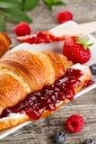鲜美新鲜的开胃新月形面包特写镜头用果子果酱,轻便小床 免版税图库摄影