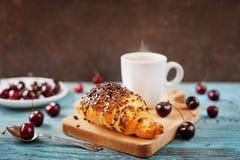 鲜美早餐用新鲜的新月形面包、咖啡和樱桃在一张木桌上 免版税图库摄影