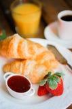 鲜美早餐:咖啡用新月形面包,橙汁,草莓 库存照片