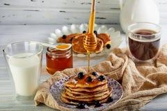 鲜美早餐A堆薄煎饼用蜂蜜给一杯牛奶、浓咖啡咖啡和蜂蜜加糖浆在木白色 免版税库存照片