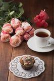 鲜美松饼和一个杯子与玫瑰的热的茶 免版税库存图片
