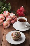 鲜美松饼和一个杯子与玫瑰的热的茶 库存图片