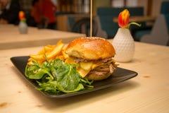 鲜美汉堡用沙拉和薯条在小餐馆桌上 库存图片