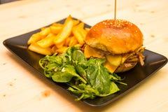 鲜美汉堡用沙拉和薯条在小餐馆桌上 免版税库存照片