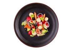 鲜美沙拉用乌贼,菜和桔子,穿戴了用在一个黑色的盘子的调味汁 在白色背景隔绝的板材的沙拉 库存图片