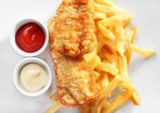 鲜美油煎的鱼、芯片和调味汁在板材 免版税库存图片