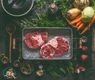 鲜美火腿飞腓节汤的成份:与骨头、根菜类、草本和香料的未加工的牛肉肉胫骨在黑暗的土气厨房用桌上 库存图片