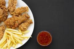 鲜美炸鸡鼓槌、辣翼、薯条、鸡招标在白色板材和酸甜调味汁在黑表面 免版税库存照片