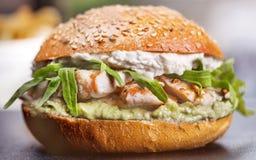 鲜美烤大虾和牛肉汉堡用莴苣和蛋黄酱在包装纸张服务在一张土气木桌上的 免版税库存照片