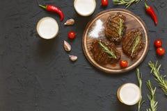 鲜美烤肉牛排和啤酒在玻璃在黑石背景,用西红柿和辣椒,迷迭香 库存照片