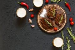 鲜美烤肉牛排和啤酒在玻璃在黑石背景,用西红柿和辣椒 免版税库存图片