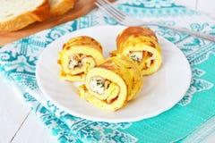 鲜美煎蛋卷充塞用乳酪和莳萝在板材和餐巾 在一个木板的切的面包,叉子 早餐煎蛋 免版税库存照片
