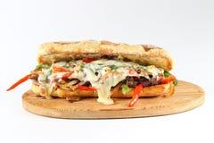 鲜美牛排三明治用葱、蘑菇和熔化普罗卧干酪乳酪 免版税库存照片