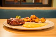 鲜美牛排用土豆和调味汁 免版税图库摄影