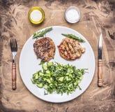 鲜美猪肉牛排用蔬菜沙拉、油和盐、刀子和叉子木土气背景顶视图关闭 免版税图库摄影