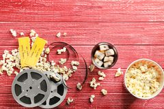 鲜美玉米花、票和电影在红色背景卷 免版税图库摄影