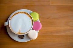 鲜美甜macarons和咖啡杯 在木背景的蛋白杏仁饼干 顶视图 图库摄影