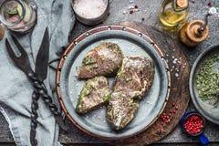 鲜美用卤汁泡的肉牛排用草本和香料格栅的或烤肉在厨房用桌上与不锈钢在土气厨房t 免版税图库摄影