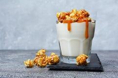 鲜美的点心 杯自创酸奶用焦糖玉米花和在黑板岩的甜调味汁上 免版税库存图片
