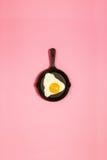 鲜美美丽的在平底锅的食物煎蛋在时兴的桃红色backgr 免版税库存图片