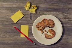 鲜美自创曲奇饼在白色圆的板材的打破的被咬住的饼干顶上的看法照片的顶面上面关闭有被粉碎的纸的s 免版税库存图片