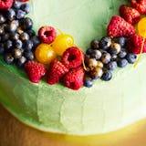 鲜美莓果蛋糕的图片在金背景的 免版税库存照片