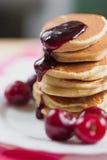 鲜美薄煎饼用新鲜的樱桃和果酱在一块白色板材 美国早餐 免版税图库摄影