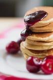 鲜美薄煎饼用新鲜的樱桃和果酱在一块白色板材 美国早餐 库存图片