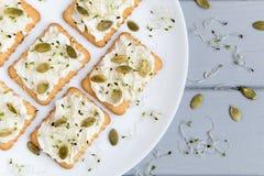 鲜美薄脆饼干用乳脂干酪、种子和绿色 在一块板材的开胃菜在灰色桌上 健康快餐,顶视图,平的位置 库存图片