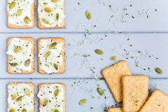 鲜美薄脆饼干用乳脂干酪、种子和绿色 在灰色桌上的开胃菜 健康快餐,顶视图,平的位置 库存图片
