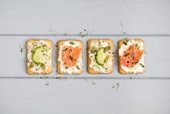 鲜美薄脆饼干用乳脂干酪,菜,鱼 在灰色桌上的开胃菜 健康快餐,顶视图,平的位置 库存图片