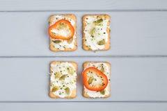 鲜美薄脆饼干用乳脂干酪,菜 在灰色桌上的开胃菜 健康快餐,顶视图,平的位置 免版税库存图片