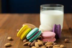 鲜美蛋白杏仁饼干和杯子牛奶用在木背景的杏仁 免版税图库摄影